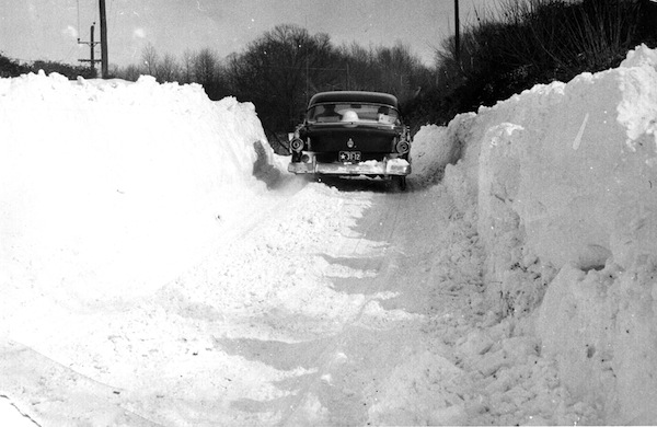 A car makes its way down a plowed road after the big snow of 1958. PHOTO COURTESY HISTORICAL SOCIETY OF CECIL COUNTY/GREAT STORMS OF THE CHESAPEAKE